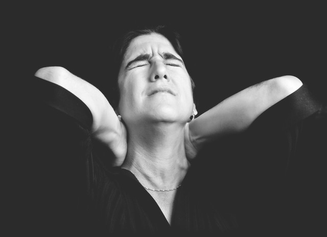 black-and-white-portrait-of-a-stressed-woman-suffering-from-neck-pain-640x0.jpg